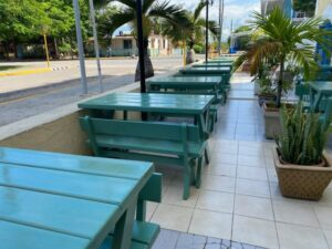 Green dining tables are standing outside near the Pullman in Cuba